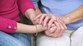 Carer holding hands with woman