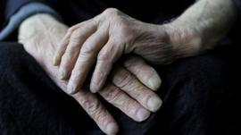Elderly man rubbing his hands together