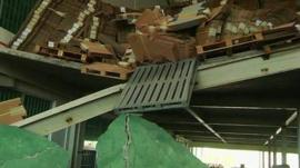 Stacks of boxes and a pallet hanging over the edge of a broken upper floor