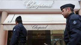 Anti-riot police officers patrol outside a Chopard shop in Cannes