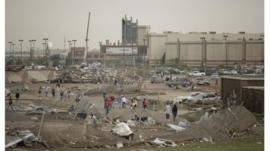 People walk through a damaged area near the Warren Theatre after a powerful tornado ripped through Moore