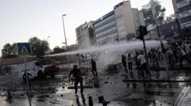 Riot police use a water cannon to disperse anti-government protesters