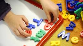 Child playing with plastic letters