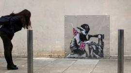 Woman looking at Banksy mural