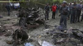 Afghan policemen inspect the site of a suicide car bomb attack in Kabul