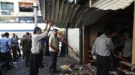 People gather at the site after bombs exploded close to a police post in the central Marjeh Square in Damascus