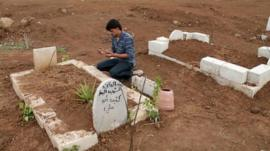 A man prays at the grave of a Free Syrian Army fighter at a cemetery at al-Karak al-Sharqi in Deraa