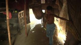 A boy wades through flood water