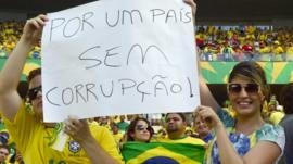 Brazilian football fans show a poster reading