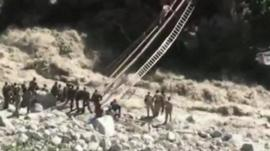 Turbulent river with rescuer climbing makeshift ladder across