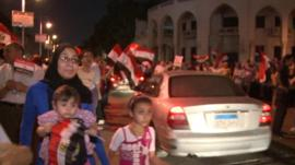 Demonstrators wave flags in Cairo
