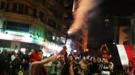 People hold fireworks in Tahrir Square on Thursday