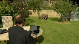 Man with laptop in Cotswolds garden