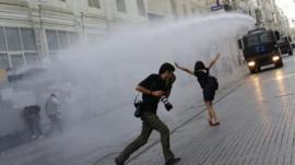 Riot police use a water cannon to disperse demonstrators during a protest in central Istanbul
