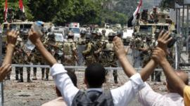 Supporters of deposed President Morsi shout slogans in front of army soldiers