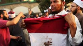 A man holds up a bloodied shirt at a pro-Morsi rally in Cairo