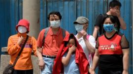 People wear masks to protect against air pollution and dust in Beijing