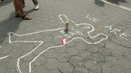 Chalk outline of person on ground and words