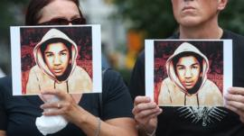 People hold photos of Trayvon Martin at a rally honouring Martin at Union Square in Manhattan on July 14, 2013 in New York City