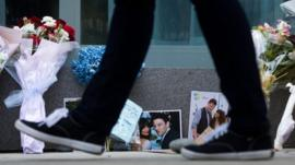 A pedestrian walks past photographs and flowers placed at a memorial for Canadian actor Cory Monteith outside the Fairmont Pacific Rim Hotel in Vancouver