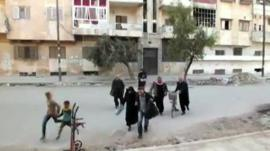 Residents run across a street in Aleppo