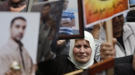 Palestinians hold pictures of their jailed relatives