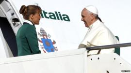 Pope Francis is welcomed by crew members as he boards a plane at Fiumicino Airport in Rome