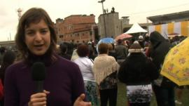 Julia Carneiro speaks to camera as Pope Francis gives a blessing in the background