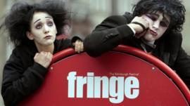 Actors pose by a sign for the Edinburgh Fringe Festival