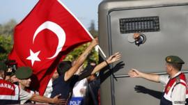Protesters run after a prison van as an unidentified defendant sticks his fist out outside the courthouse in Silivri