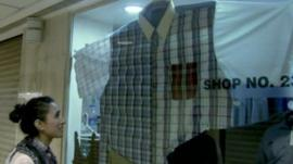 Anita Rani looks at a shirt in an over-size clothes shop in Mumbai