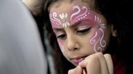 A Muslim girl has her face decorated as Muslims celebrate Eid al-Fitr in Valby, Copenhagen