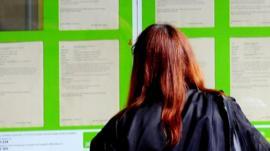 Woman looking in Job Centre window