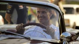 British former Formula One racing driver, sits behind the wheel of a 1955 Pontiac convertible car