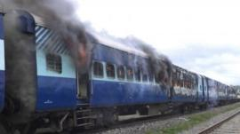 Coaches of the Rajya Rani Express train burn after a mob set it on fire