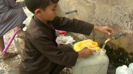 Young boy filling container with water