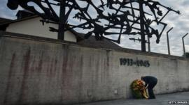 German Chancellor Angela Merkel lays a wreath while visiting the Dachau concentration camp memorial