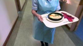 Nurse carrying tray of food
