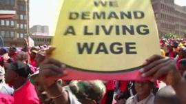 Protestors holding placards that read 'we demand a living wage'