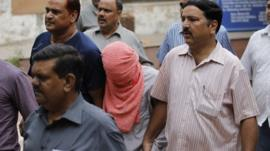 The teenager convicted of taking part in a fatal gang rape is escorted by police outside the Juvenile justice board in New Delhi
