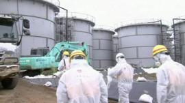 Workers at the Fukushima plant wearing white radiological protection suits, masks and hard hats