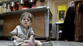 A Syrian woman who fled her home because of Syria's civil war prepares a meal in the kitchen as her child looks at the camera at the Kertaj Hotel in Damascus, Syria