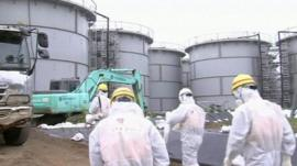 Workers at the plant wearing radiological protective suits, hard hats and masks walking towards large containers