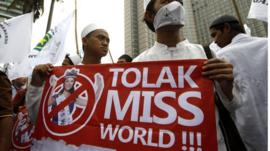 Protesters display a banner during a protest calling for the cancellation of the Miss World pageant in Jakarta
