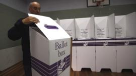 An electoral officer at the Balmoral polling station puts together ballot boxes and voting booths in Sydney