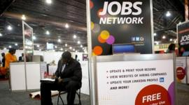 A job-seeker completes an application at a career fair