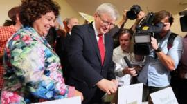 Australian Prime Minister Kevin Rudd casts his vote with his wife Therese Rein at a polling station in Brisbane