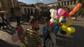 Children hold balloons on a street in Damascus