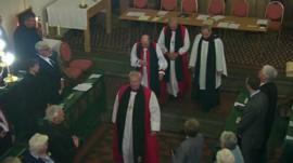 Four male bishops inside a Church.
