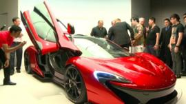 Man photographing a Mclaren supercar